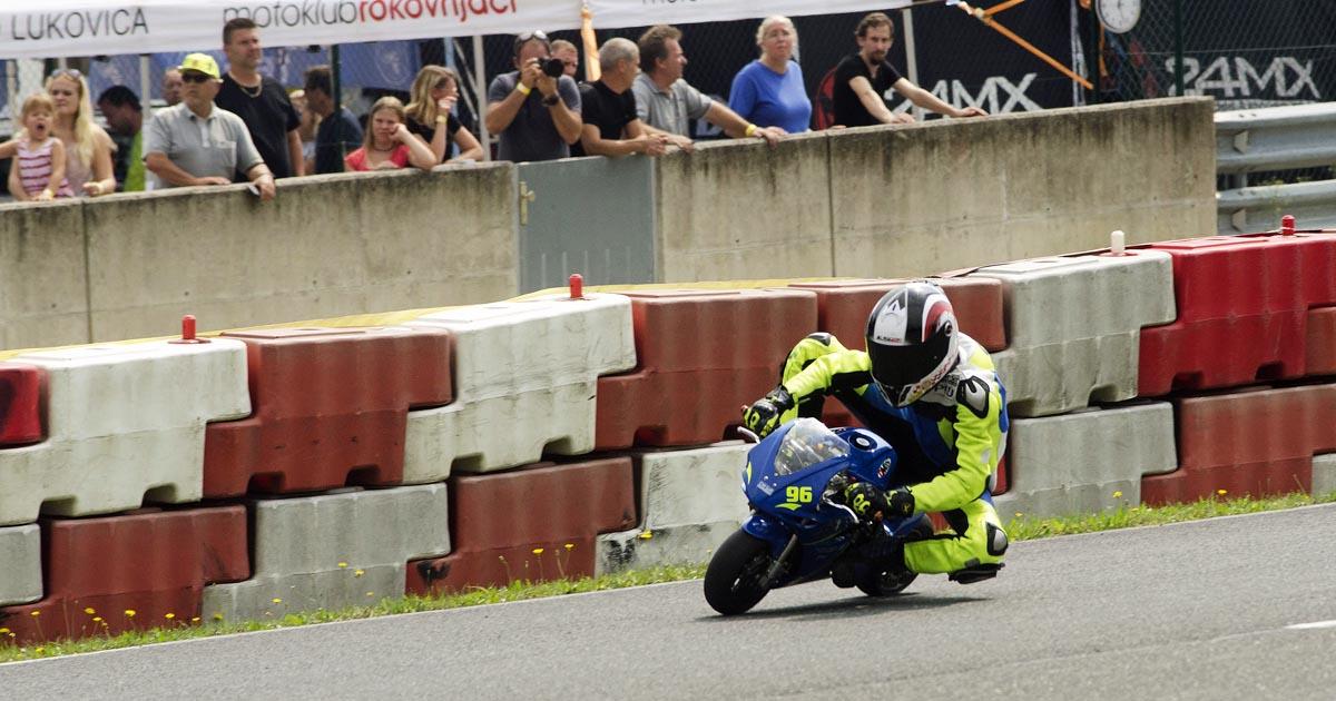 Publika in fotografi gledajo dirkača