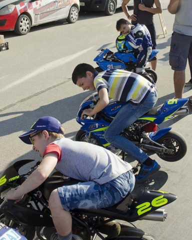 Mladi minimoto dirkači se veselijo po koncu dirke